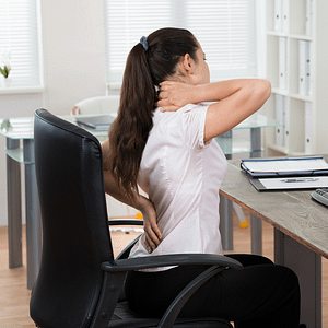 Lady sitting at chair clutching neck and back in pain